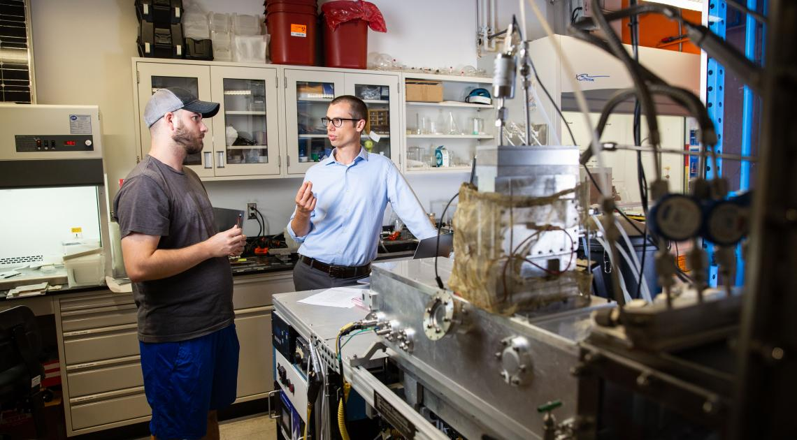 Arizona State University Assistant Professor, Zachary Holman (right), talks with Doctoral Student, Peter Firth, next to a prototype of a nano-particle deposition tool. Holman was awarded a Moore Inventor Fellowship to further develop a technique that can add beneficial properties to ordinary surfaces through nano-particle coatings. Photographer: Deanna Dent/ASU